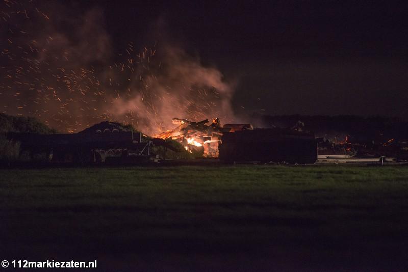 Grote hoop stookhout in brand bij landbouwbedrijf in Sint-Maartensdijk